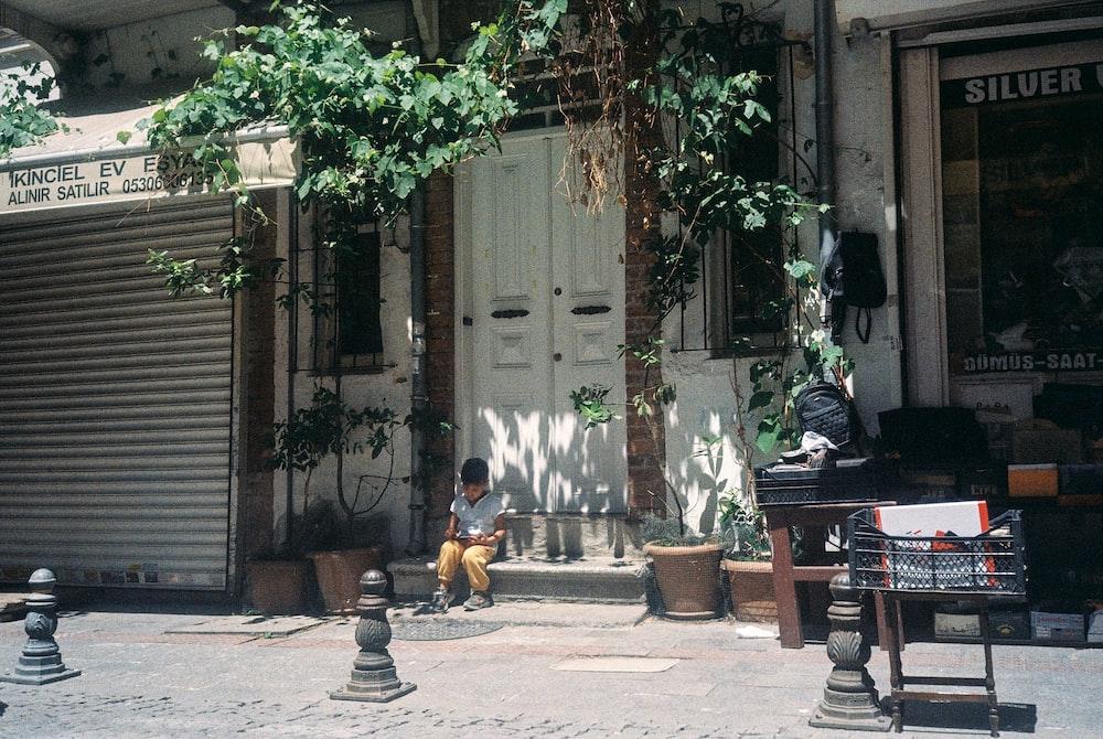 2 boys sitting on bench near white wooden door during daytime