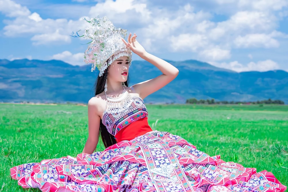 woman in red and white floral tube dress wearing white floral headdress