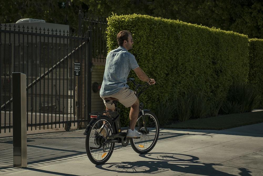 man in blue dress shirt riding on black bicycle during daytime