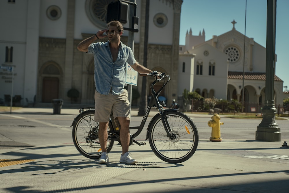 man in blue dress shirt and brown shorts standing beside black bicycle during daytime