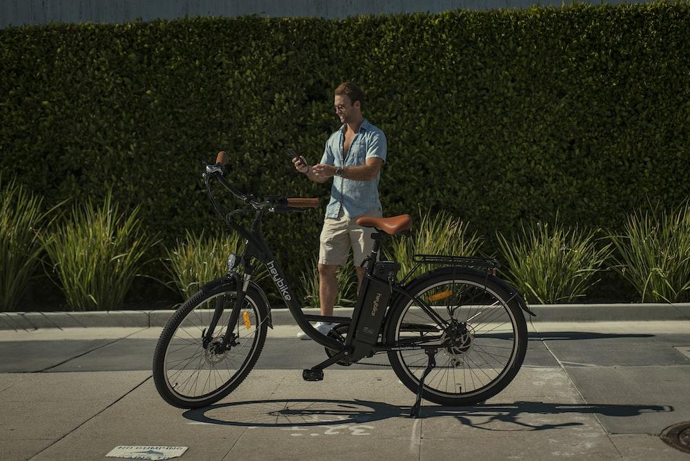 man in white polo shirt riding on black bicycle during daytime