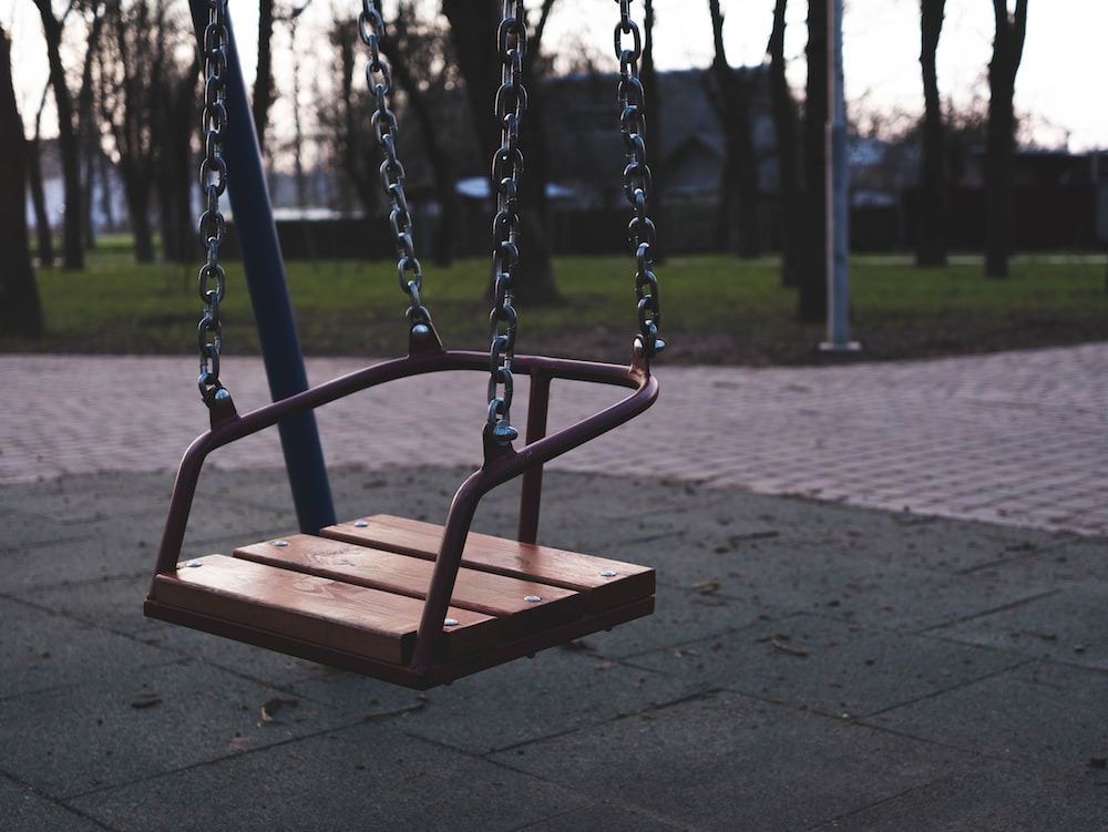 brown wooden swing chair on park during daytime