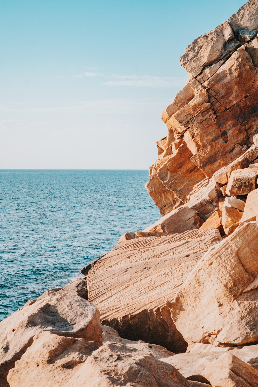 brown rock formation beside blue sea during daytime