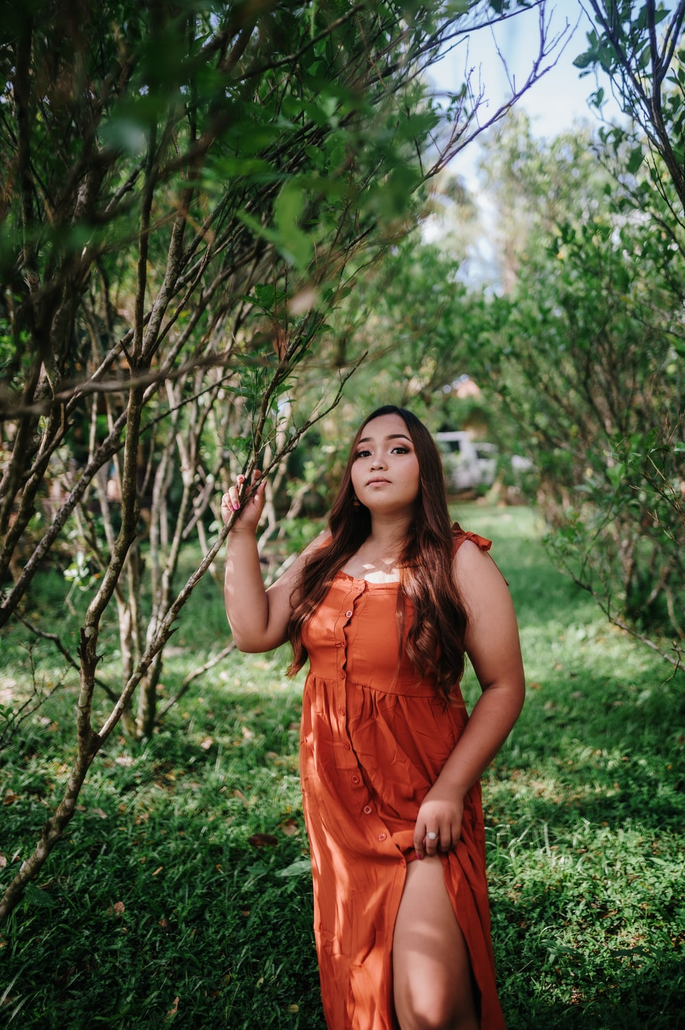 woman in orange sleeveless dress standing on green grass field during daytime