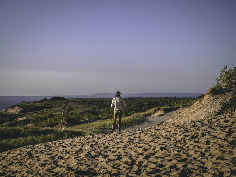woman in white shirt and black pants walking on brown sand during daytime