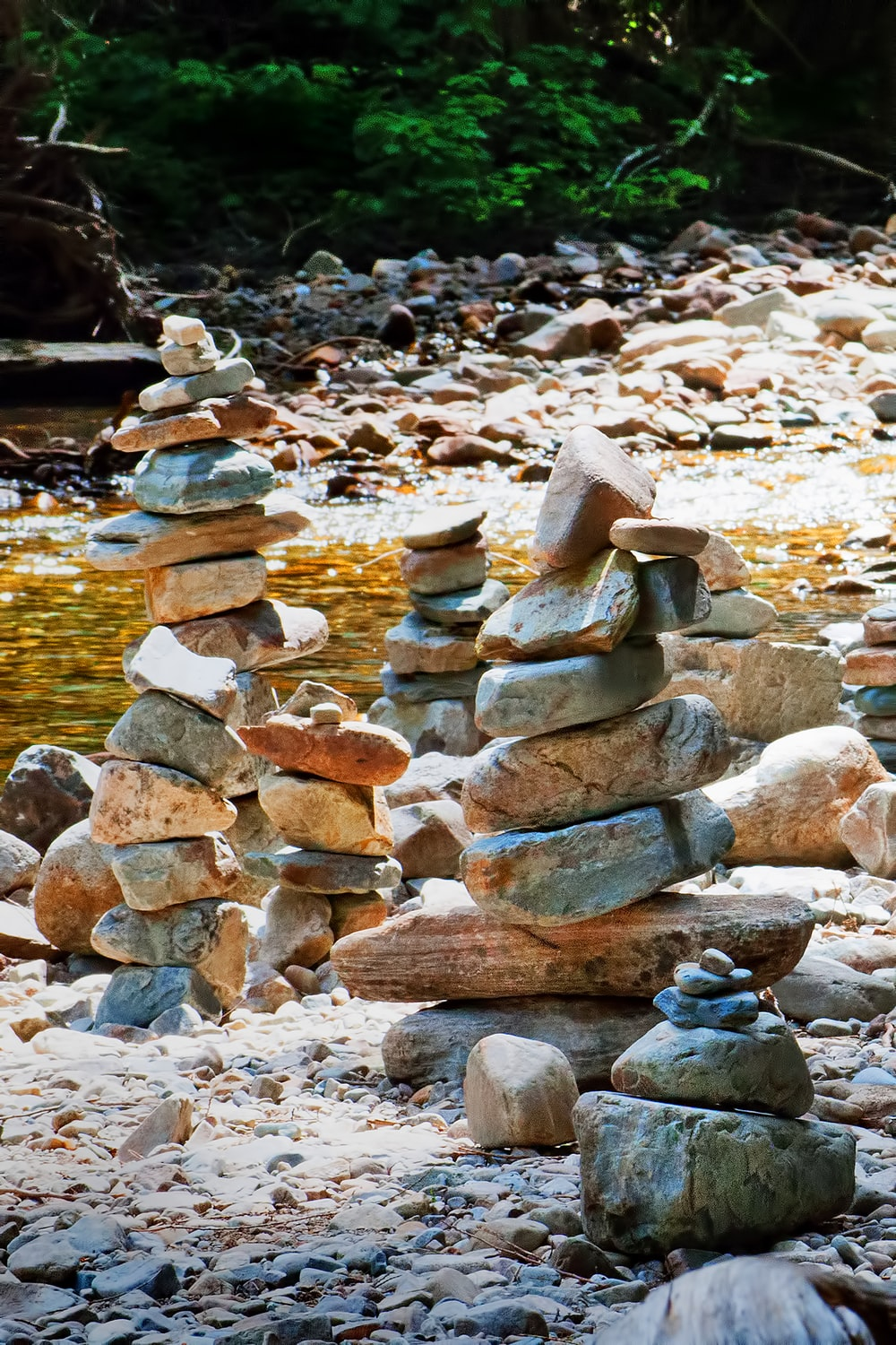 stack of stones near body of water during daytime