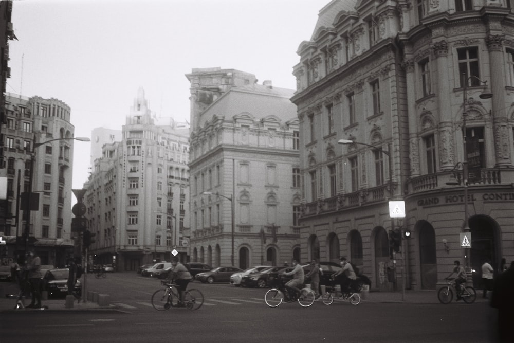 grayscale photo of people riding motorcycle near building