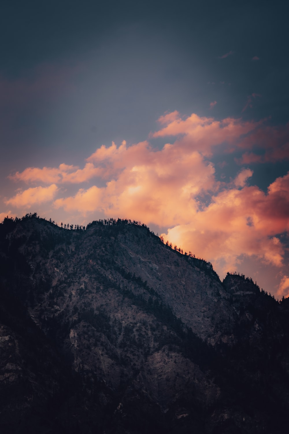 green and brown mountain under cloudy sky during sunset