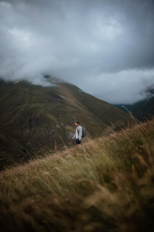 man in white jacket walking on green grass field during daytime