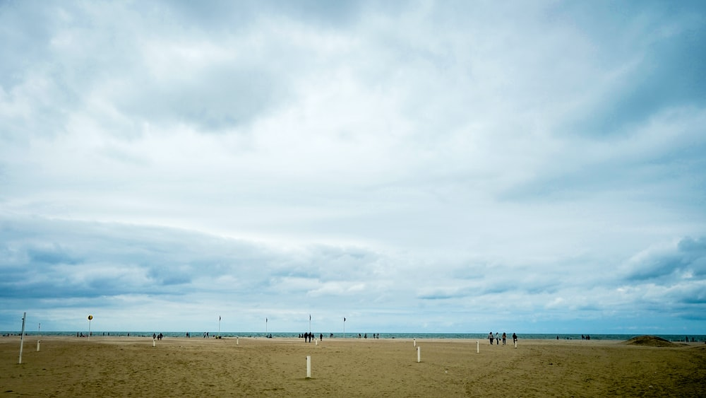people walking on brown sand under white clouds during daytime