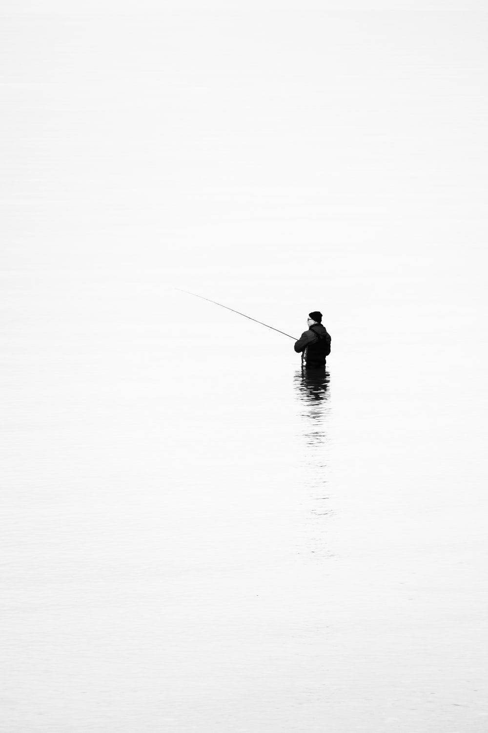 person in black jacket fishing on water