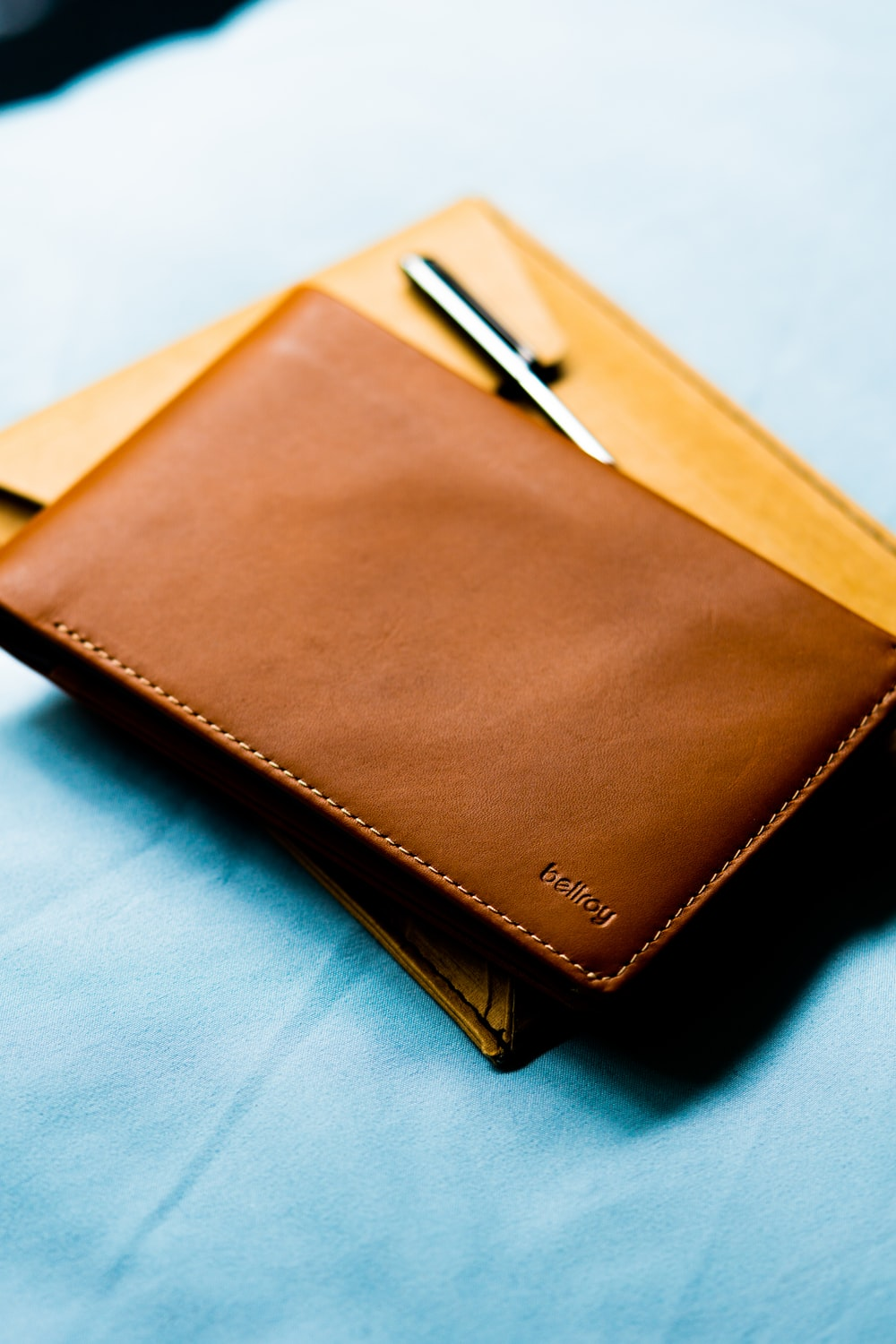 brown leather wallet on white textile