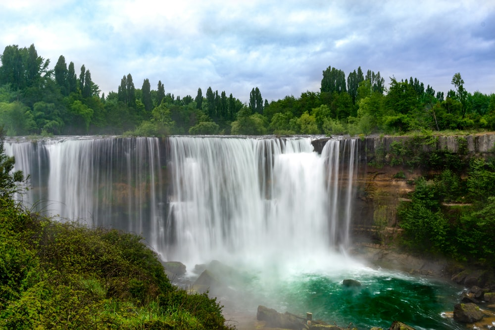 waterfalls near green trees under white clouds during daytime