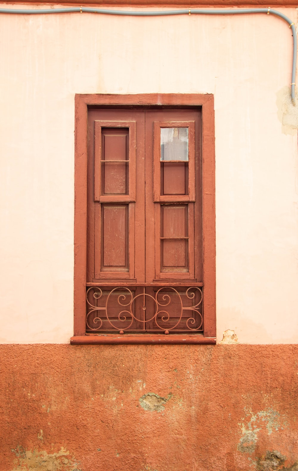 brown wooden door on white concrete wall