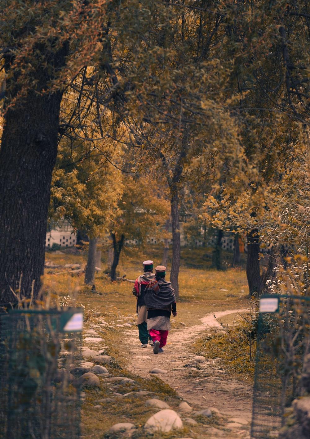 man in brown jacket and black pants walking on pathway