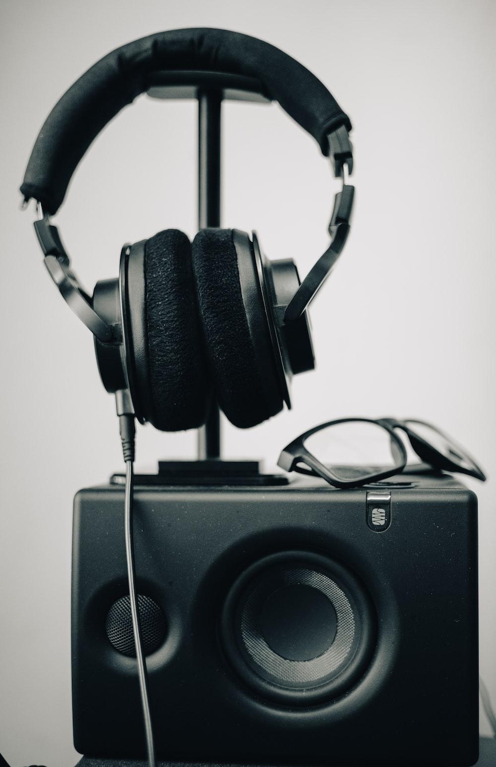 black and silver headphones on black speaker
