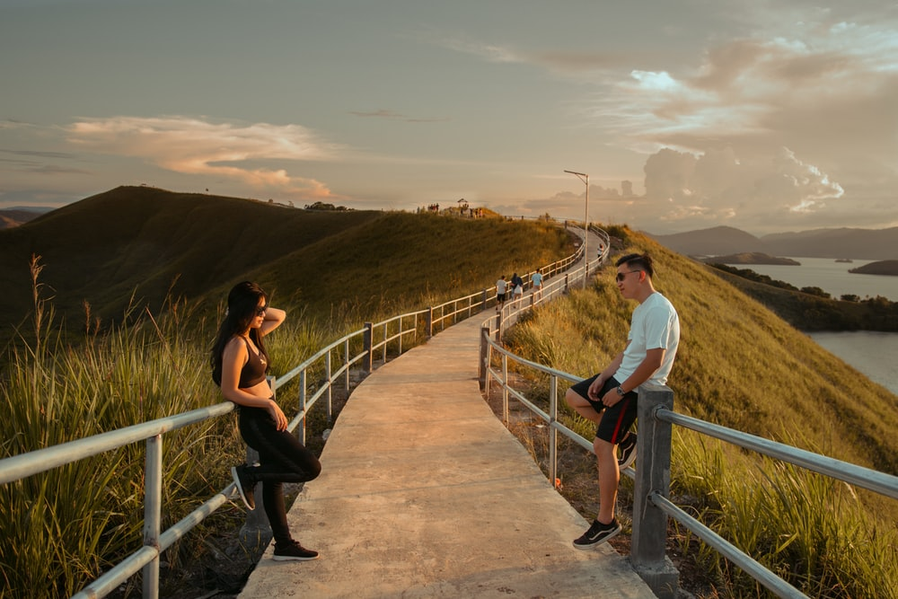 man and woman standing on brown wooden bridge during daytime