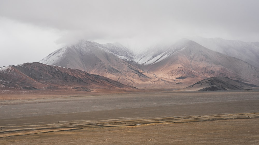 brown and white mountains under white sky during daytime