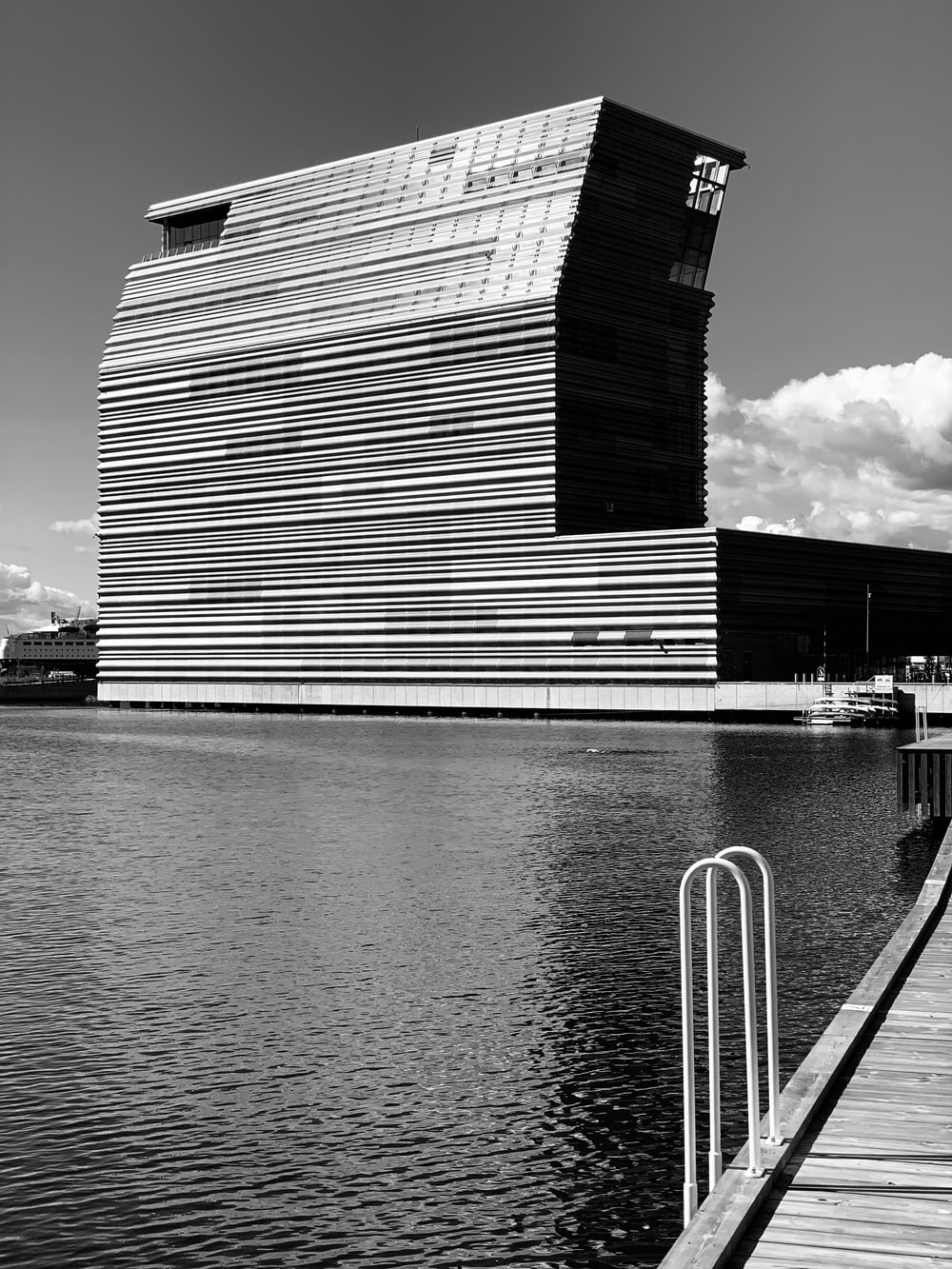 grayscale photo of a building near the sea