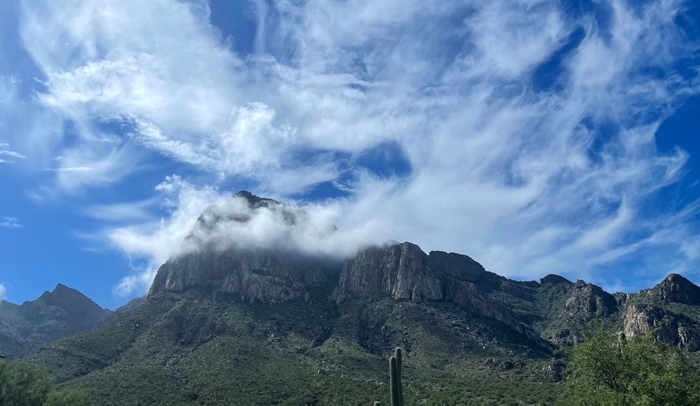 green and gray mountain under blue sky and white clouds during daytime