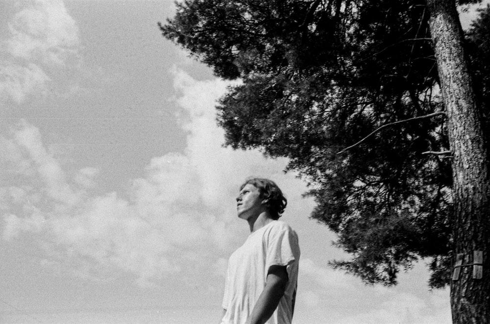 man in white t-shirt standing near tree