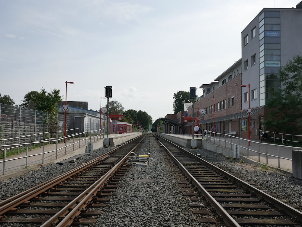 red and white train rail near red and white concrete building during daytime