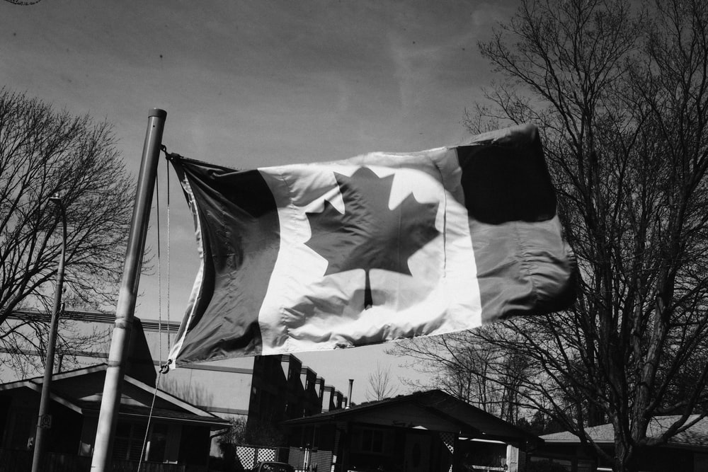 grayscale photo of flag of us a on pole