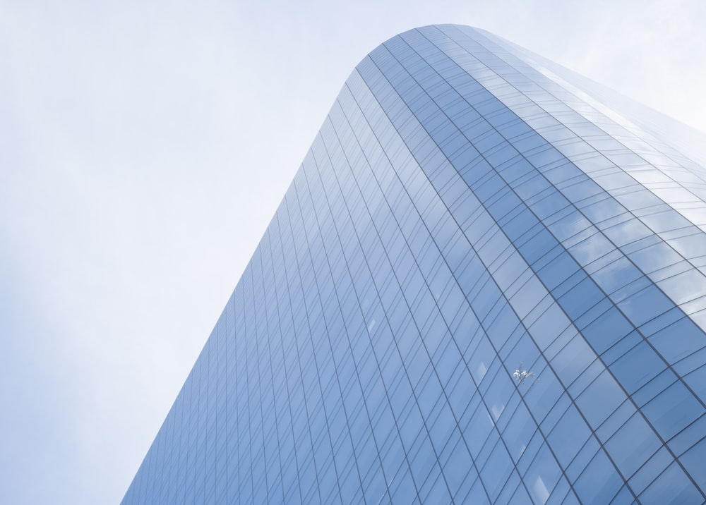 white and blue glass walled high rise building