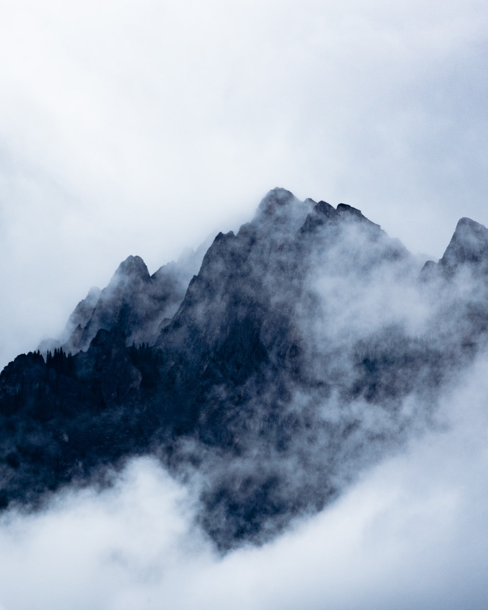 black mountain covered by clouds