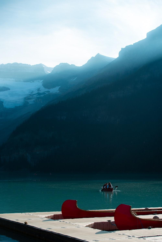 2 people on boat on lake during daytime