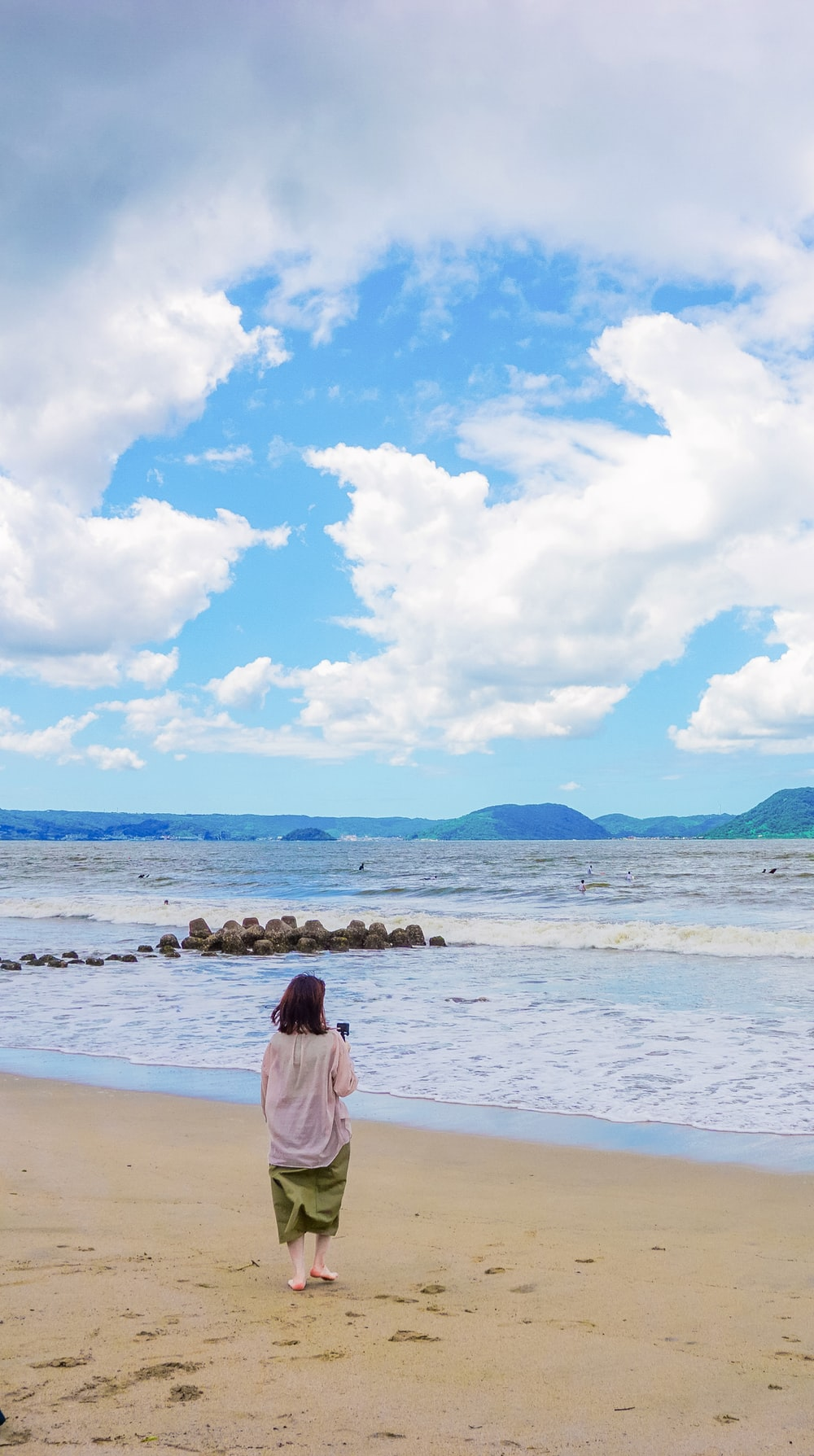 woman in pink dress sitting on white sand near body of water during daytime