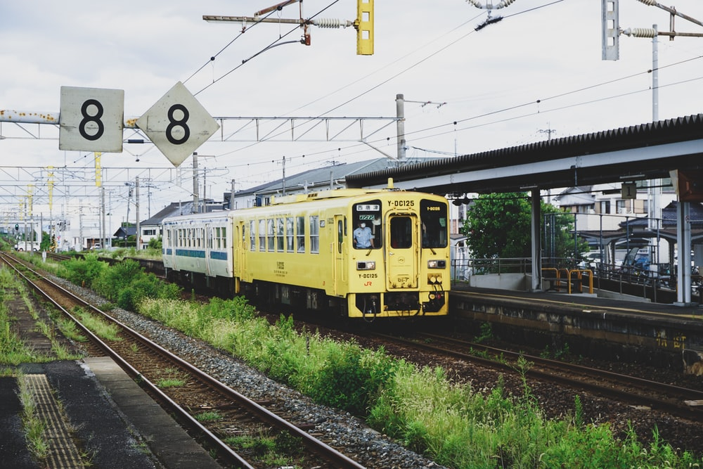 yellow and white train on rail tracks