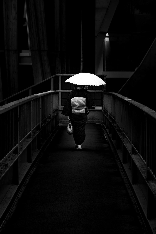 grayscale photo of man in jacket holding umbrella walking on bridge