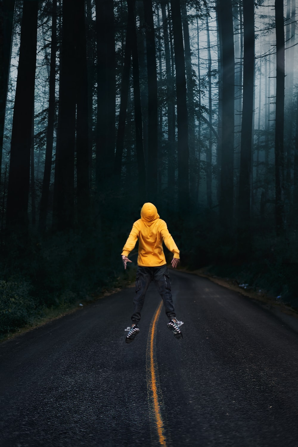 man in yellow hoodie and black pants riding bicycle on road during daytime
