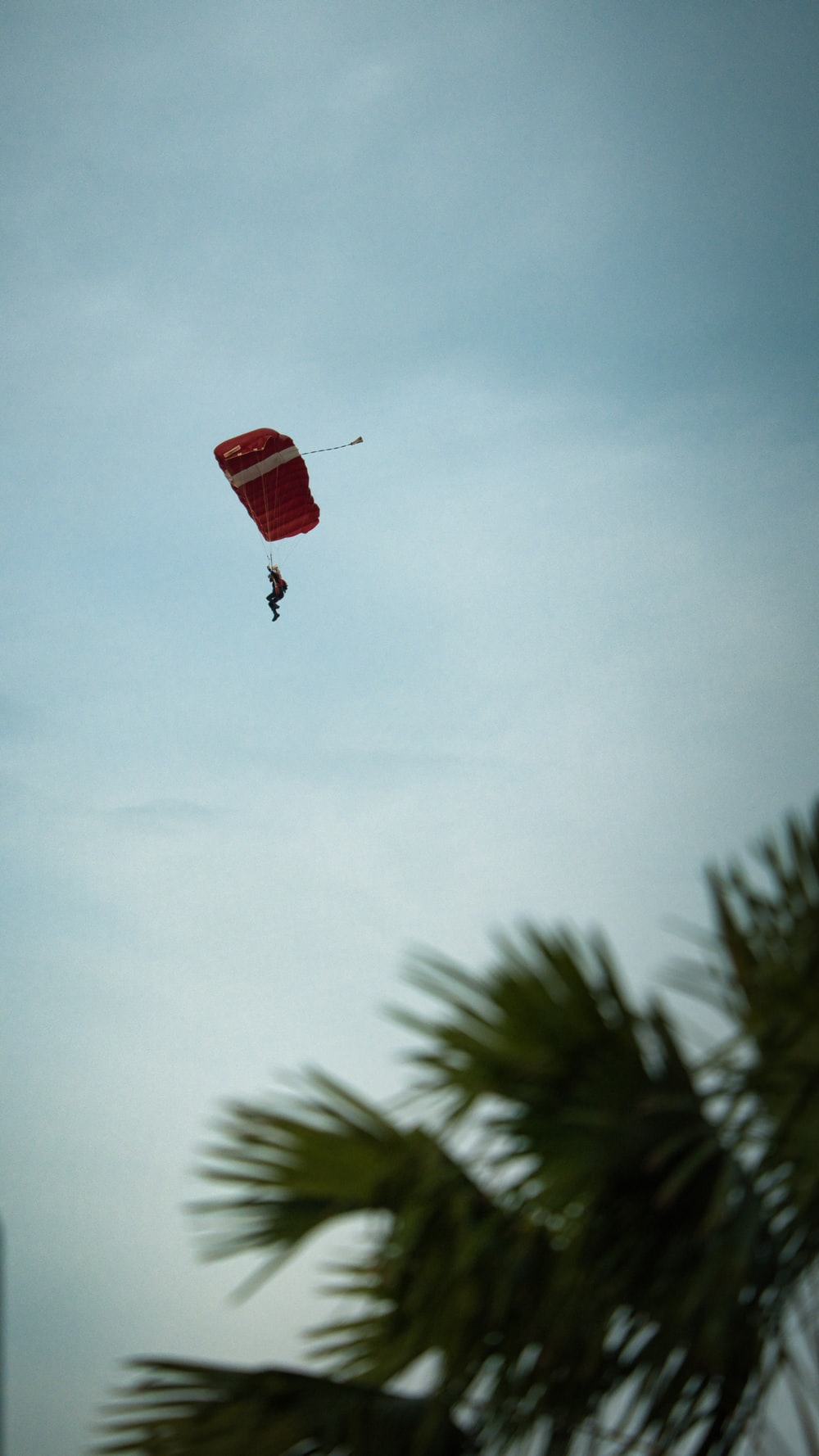 person in red parachute under white sky during daytime