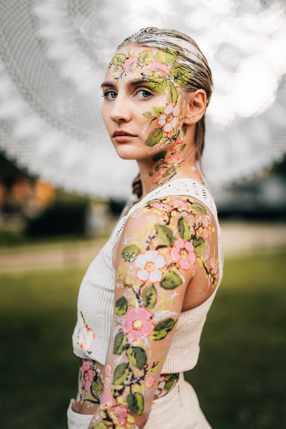 woman in white green and pink floral dress with green flower headdress