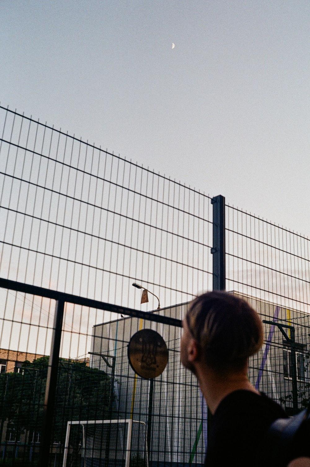 woman in black shirt standing near black metal fence during daytime