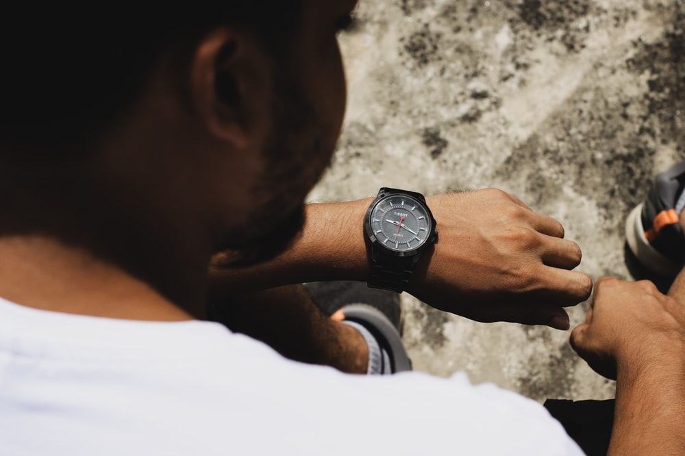 man in white shirt wearing black round analog watch