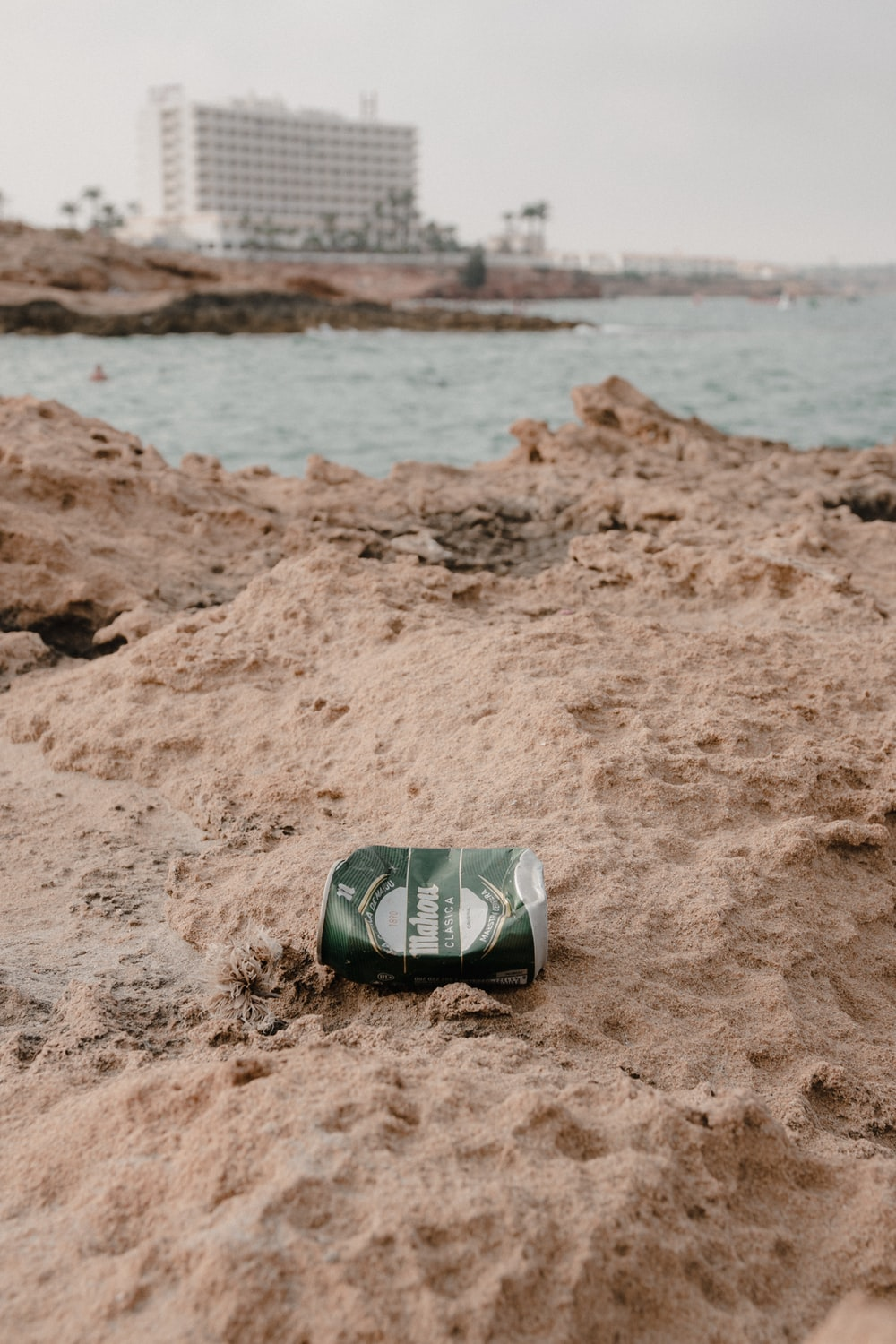 green and white labeled can on brown sand near sea during daytime