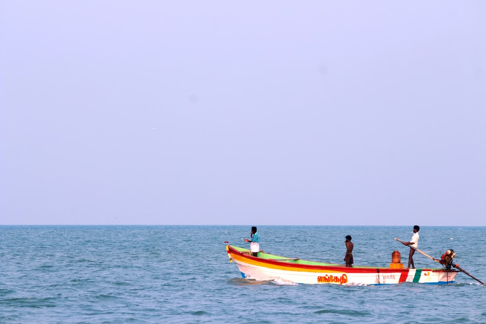 2 people riding on red and white boat on sea during daytime