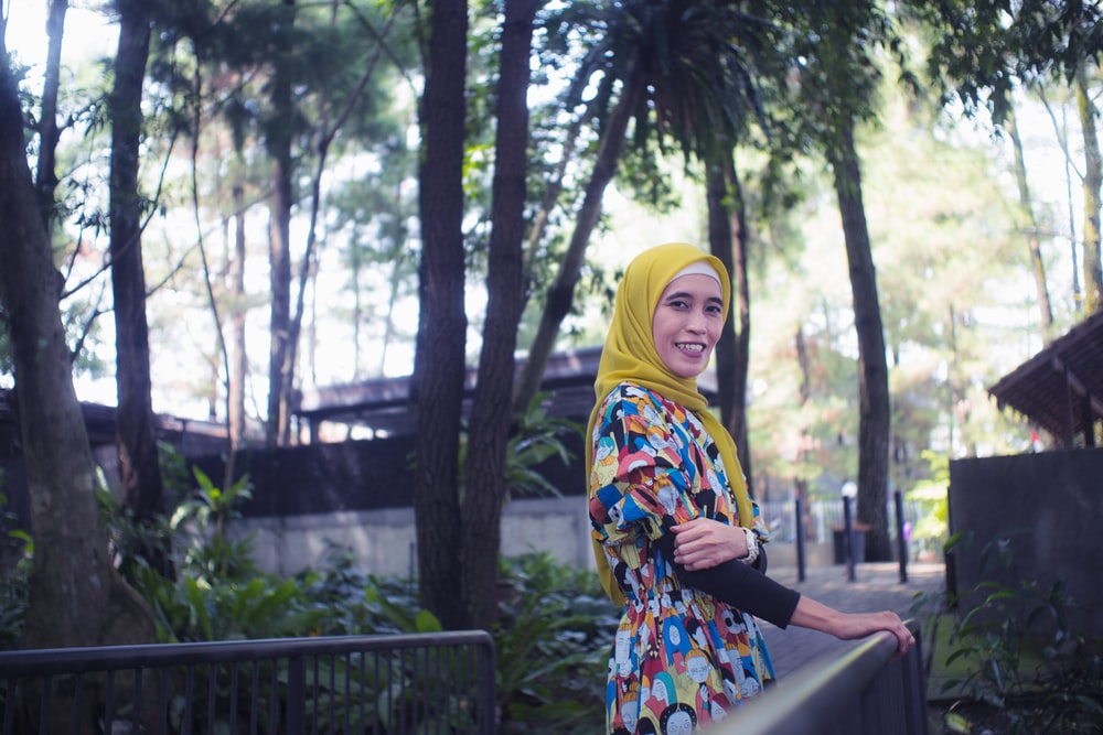 woman in yellow hijab standing near green trees during daytime