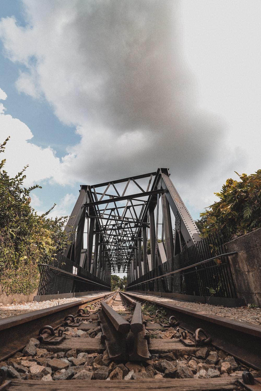 gray metal bridge under white clouds during daytime
