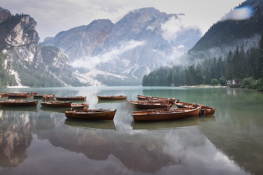 brown boat on calm water near snow covered mountain during daytime