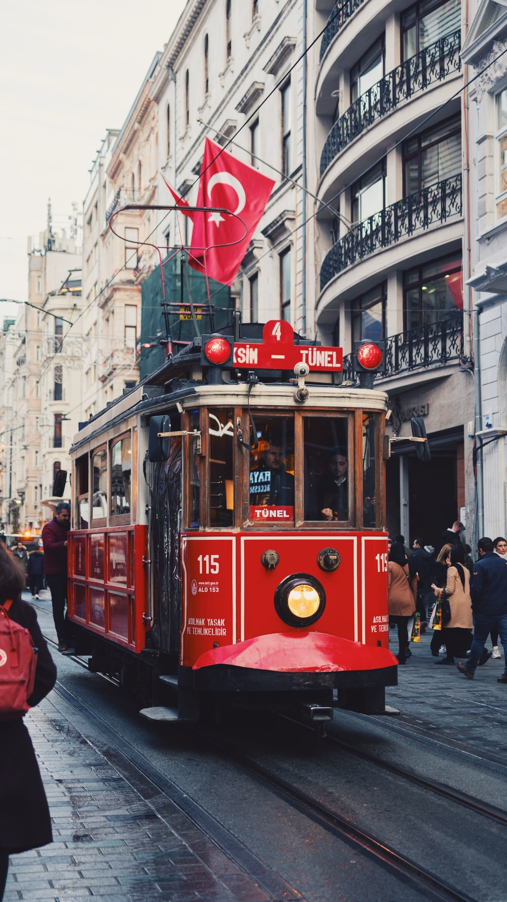 red tram on the street during daytime