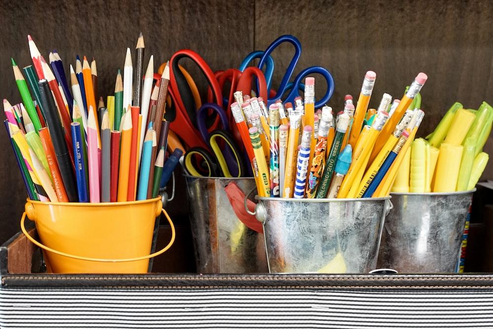assorted color pencils in yellow bucket