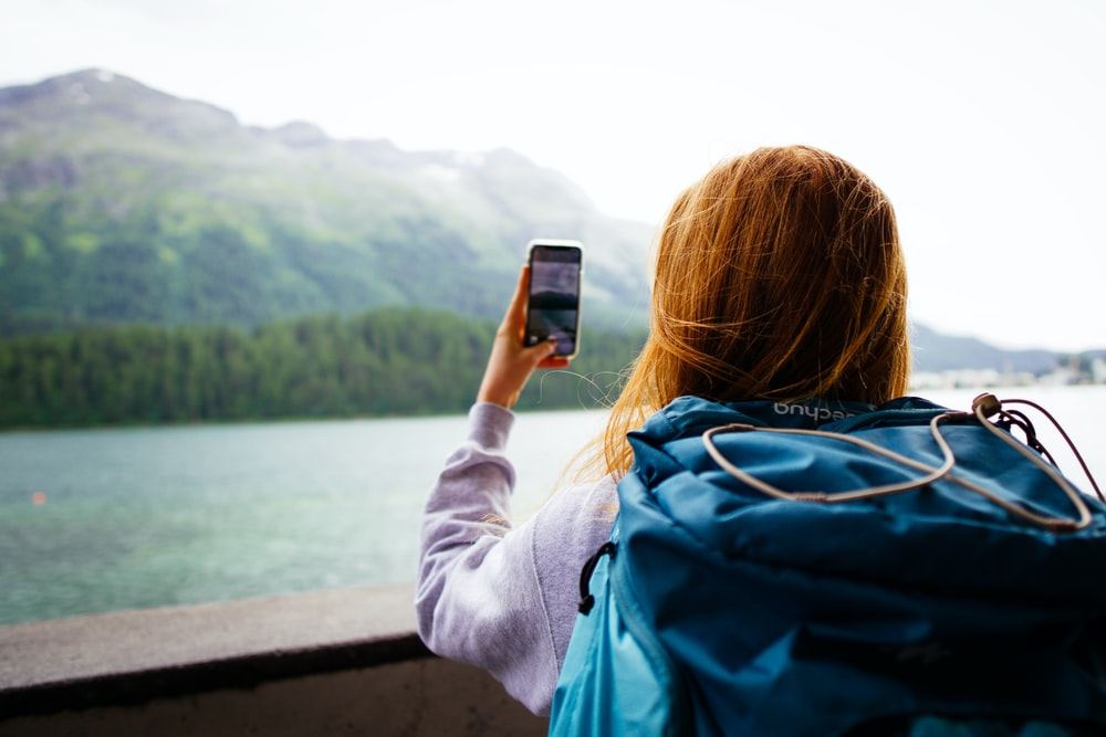 woman in gray jacket holding smartphone
