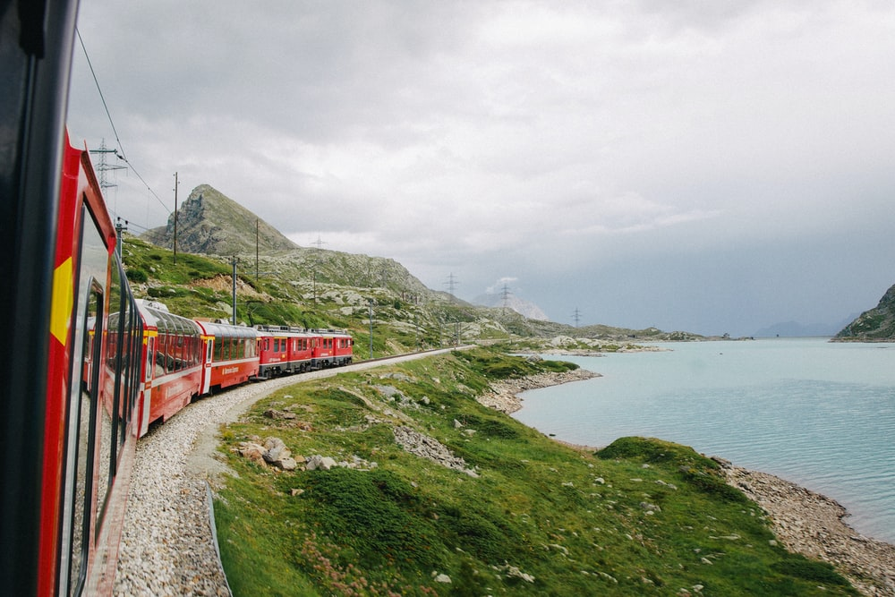 red train on rail near body of water during daytime