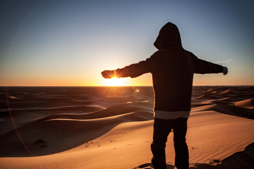 silhouette of person standing on sand during sunset