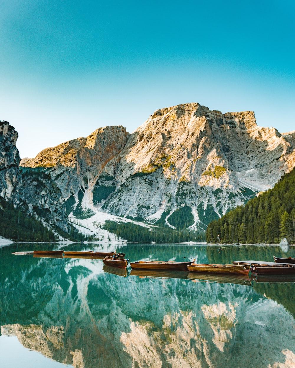 brown wooden dock on lake near mountain range