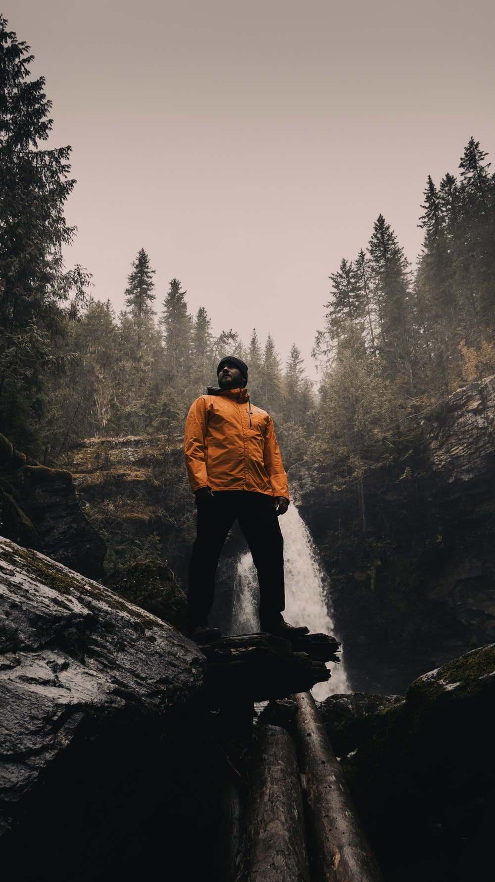 man in brown jacket standing on rock near waterfalls during daytime